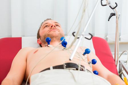 Male patient having ECG electrocardiogram in hospital Stock Photo