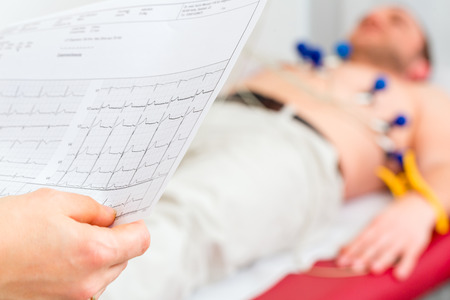 Female doctor analyzing ECG electrocardiogram of patient in hospital Stock Photo