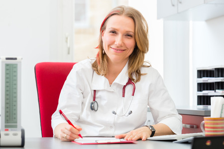 gynaecologist: Young gynaecologist writing medical prescription in surgery at desk Stock Photo