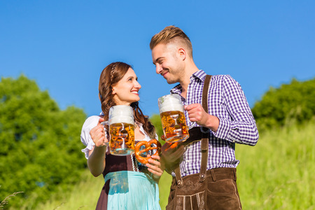 German couple in Tracht with beer and pretzel photo