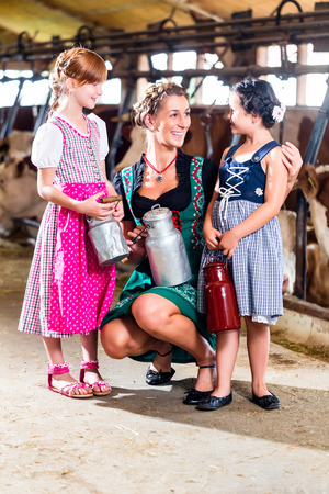 children cow: Bavarian family with milk can on cow farm