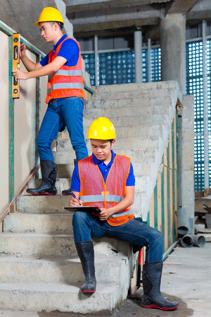 walling: Asian Indonesian builder or craftsman with hardhats, checklist and a bubble level controlling or checking a walls of a tower building or construction site