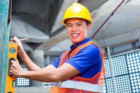 walling: Asian Indonesian builder or craftsman with hardhat and bubble level controlling or checking a wall of a tower building or construction site