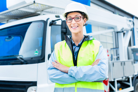 Female engineer standing in front of truck on building or construction site Stock Photo