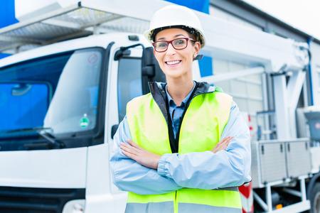 camion grua: Ingeniero de sexo femenino de pie delante de camión en la construcción o la construcción del sitio