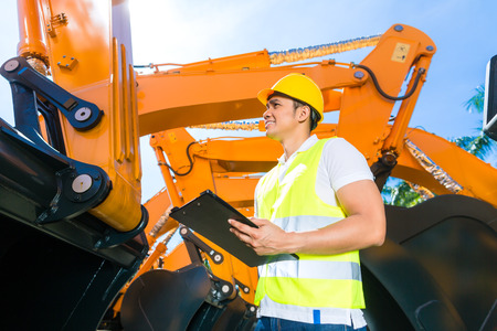 site: Asian worker controlling construction machinery of building site or mining company Stock Photo