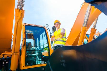 Travailleur asiatique debout sur les machines de construction sur chantier Banque d'images - 33784263