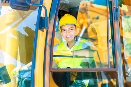 mining machinery: Asian driver sitting in cockpit of construction machinery of building site or mining or rental company Stock Photo