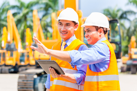 job site: Asian engineer controlling construction machinery of construction site or mining company