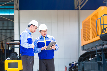 mining machinery: Asian engineer controlling construction machinery of construction site or mining company