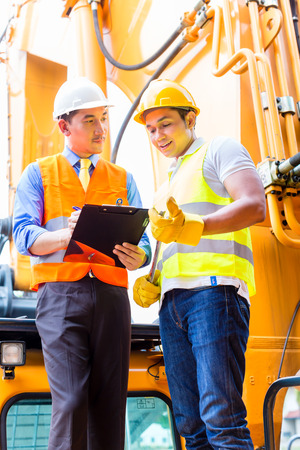 motor mechanic: Asian motor mechanic discussing with foreman task list in vehicle workshop Stock Photo