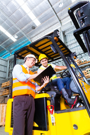 Asian fork lift truck driver discussing checklist with foreman in warehouse photo