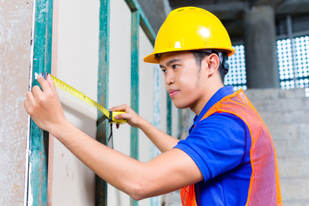 walling: Asian Indonesian builder or craftsman with hardhat and measure tape controlling or checking a wall of a tower building or construction site Stock Photo