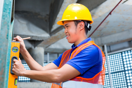 Asian Indonesian builder or craftsman with hardhat and bubble level controlling or checking a wall of a tower building or construction site photo