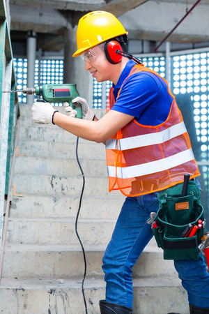 walling: Asian Indonesian builder or worker drilling with a machine or drill, ear protection and hardhat or helmet  in a wall of a tower building or construction site