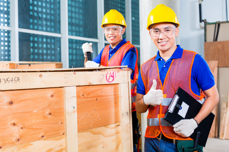Two Asian Indonesian industrial or construction workers controlling with a checklist a delivery on a tower building site and open a wood box or cargo container with a crowbar photo