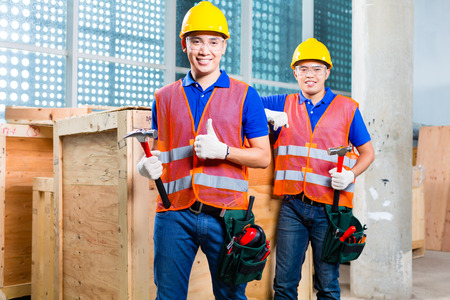 Two Asian Indonesian  construction worker on a tower building site close a wood box or cargo container with hammer and nail photo