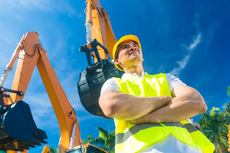 company: Asian worker standing in front of construction machinery of building site or rental company Stock Photo