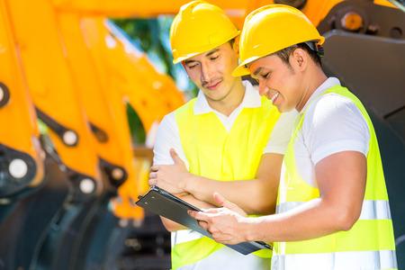 Ingeniero de control de maquinaria de construcción asiático de emplazamiento de la obra o empresa minera Foto de archivo