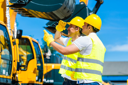 sites: Asian worker at construction machinery of construction site or mining company