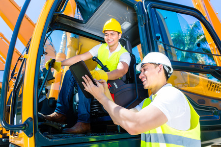 building site: Asian construction machinery driver discussing with foreman blueprints on pad or tablet computer of building site