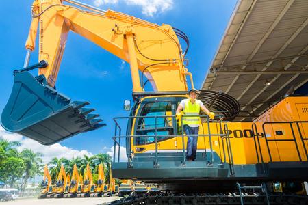 maquinaria pesada: Asia permanente conductor en maquinaria de construcción en el sitio de construcción