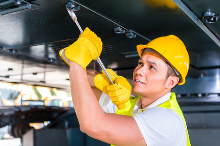 machinery: Asian motor mechanic working on construction or mining machinery in vehicle workshop