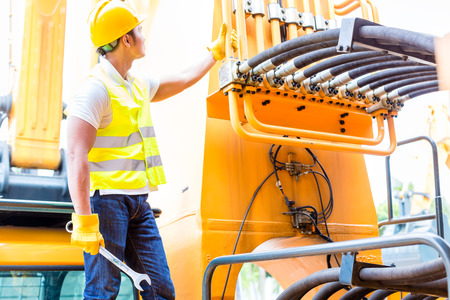 mining machinery: Asian motor mechanic standing in front of construction or mining machinery in vehicle workshop