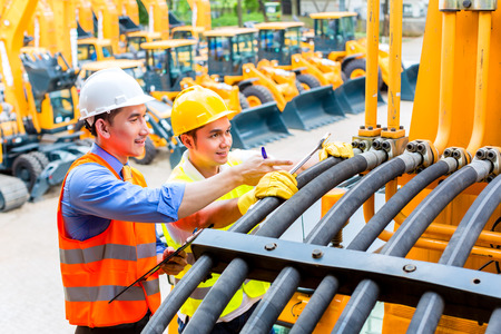 mining: Asian motor mechanic discussing with engineer task list in construction machine workshop Stock Photo