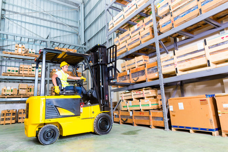 fork: Asian fork lift truck driver lifting pallet in storage warehouse