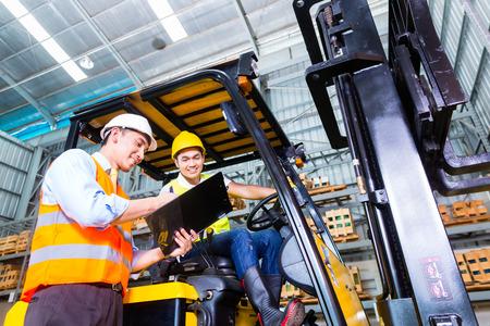 camion: Conductor carretilla elevadora tenedor de Asia discutir con lista de verificaci�n capataz en almac�n Foto de archivo