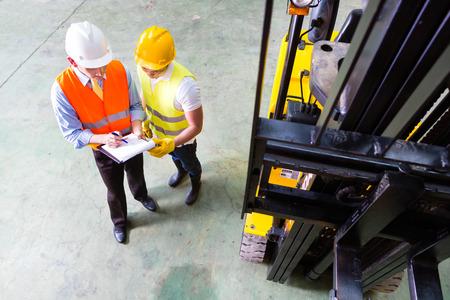 montacargas: Conductor carretilla elevadora tenedor de Asia discutir con lista de verificaci�n capataz en almac�n Foto de archivo