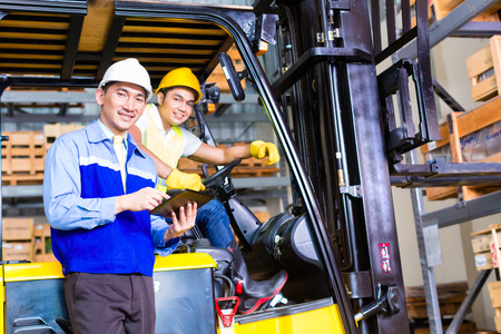 warehouse equipment: Asian fork lift truck driver discussing checklist with foreman in warehouse
