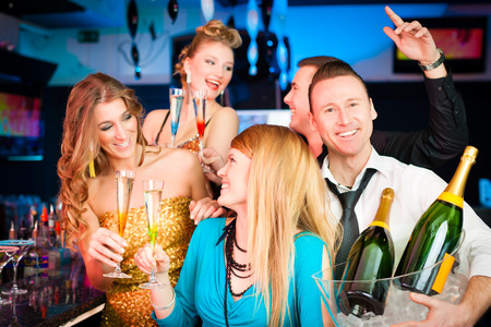 Young people in club or bar drinking champagne and having fun; one man is looking into the camera photo