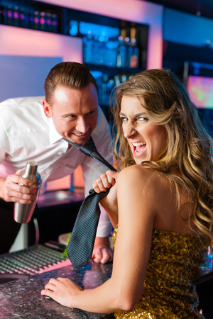 Woman in club dragging the barkeeper over the bar counter photo