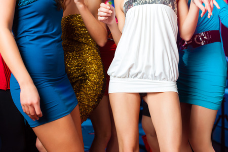 Young people dancing in club or disco, here long legs to be seen