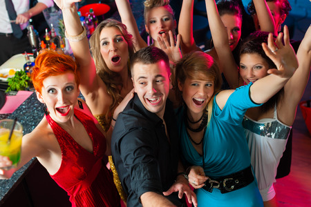 Young people dancing in club or disco, the girls and boys having fun photo
