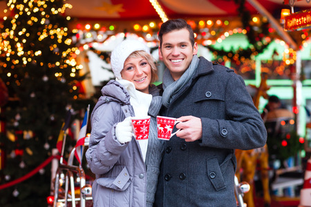 Man and woman or couple or friends drinking during advent season or holiday in front of a carousel a cup or mug of spiced wine or eggnog on the Christmas or Xmas market