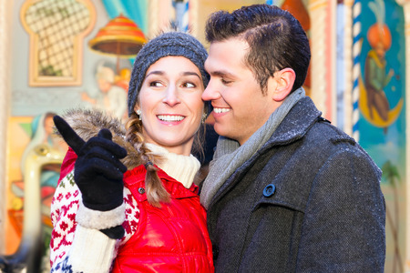 winter couple: Man and woman or  a couple  or friends during advent season or holiday in front of a carousel or merry-go-round on the Christmas or Xmas market Stock Photo
