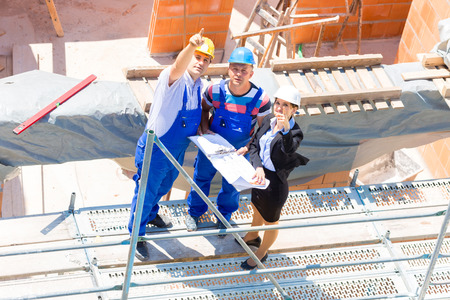 tallyman: Construction site Team or architect and builder or worker with helmets discuss on a scaffold construction plan or blueprint or checklist Stock Photo