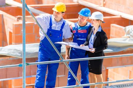 Bouwplaats Team of architect en bouwer of werknemer met helmen te bespreken op een steiger constructie plan of blauwdruk of checklist Stockfoto