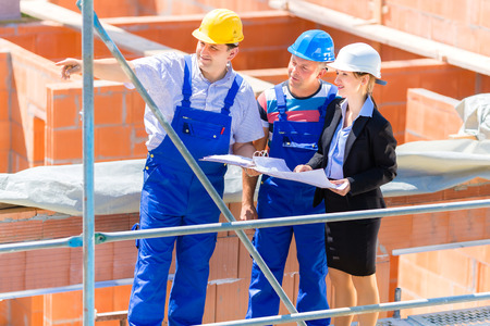 female worker: Construction site Team or architect and builder or worker with helmets discuss on a scaffold construction plan or blueprint or checklist Stock Photo