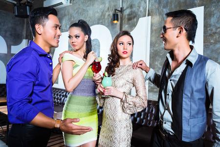 2 つのアジアの若くてハンサムなパーティー人カップル豪華で派手な夜のクラブで飲むカクテル