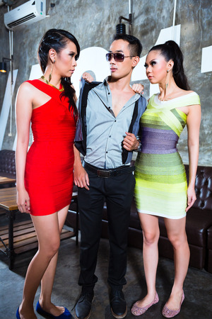 women fighting: Jealous Asian party people women fighting for man in fancy and luxurious night club Stock Photo