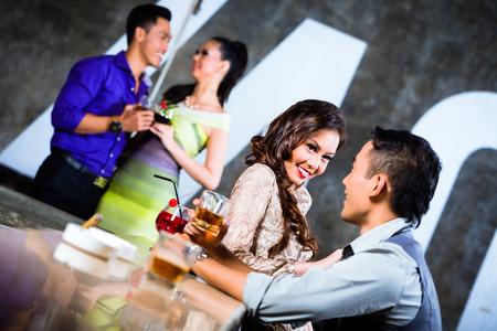 2 つのアジアの若くてハンサムなパーティー人カップルいちゃつく、豪華で派手な夜のクラブのバーで飲んで