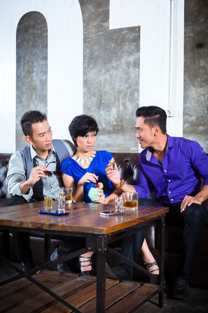harass: Asian party people man harass woman with her boyfriend in night club by inviting her to a drink