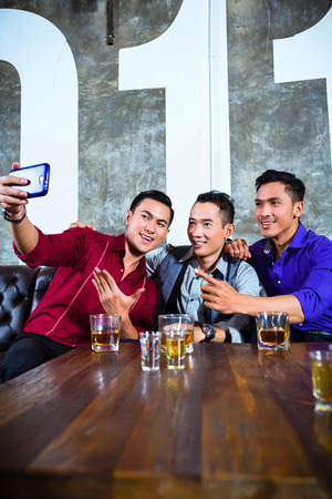 asian trees: Asian party people group of young friends taking pictures or selfies with their mobile or cell phone in fancy night club