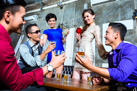 Asian young and handsome group of party people or friends drinking cocktails and shots in fancy night club Stock Photo