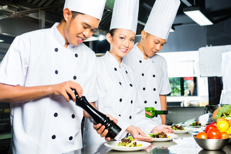 hotel kitchen: Asian Indonesian chef along with other cooks in restaurant or hotel commercial kitchen cooking, finishing dish or plate