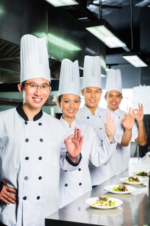 Asian Chefs in restaurant kitchen cooking photo